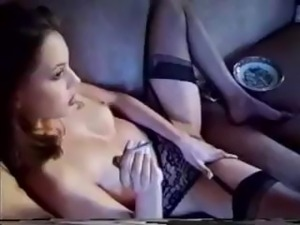 Brunette has a smoke while she plays with her trimmed pussy