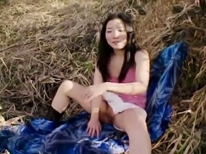 Naughty asian teen chick shows tits and pussy outdoors