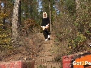 Tall and slender blondie in the park undresses and pisses